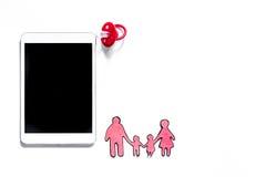 Maqueta para el concepto de la adopción PC cerca del pacificador del bebé, silueta de papel de la familia en el copyspace blanco  Imagenes de archivo