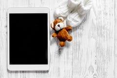 Maqueta para el concepto de la adopción Tablet PC cerca de botines y juguetes en copyspace de madera ligero de la opinión superio Imagen de archivo