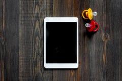 Maqueta para el concepto de la adopción Tablet PC cerca del pacificador del bebé en copyspace de madera oscuro de la opinión supe Fotografía de archivo libre de regalías