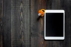 Maqueta para el concepto de la adopción Tablet PC cerca del pacificador del bebé en copyspace de madera oscuro de la opinión supe Imagen de archivo