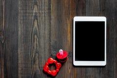 Maqueta para el concepto de la adopción Tablet PC cerca del pacificador del bebé en copyspace de madera oscuro de la opinión supe Imagenes de archivo
