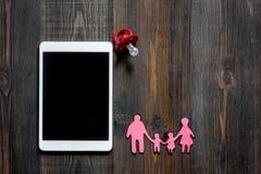Maqueta para el concepto de la adopción Tablet PC cerca del pacificador del bebé en copyspace de madera oscuro de la opinión supe Foto de archivo libre de regalías