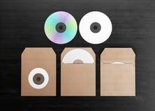 Maqueta para la identidad de marcado en caliente DVD en blanco en el empaquetado de la cartulina Fotos de archivo libres de regalías