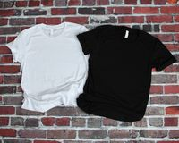 Maqueta plana de la endecha de la camiseta blanca y de la camiseta negra en backgr del ladrillo fotos de archivo