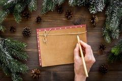 Maqueta por el Año Nuevo 2018 La mano escribe en la hoja de papel cerca de ramas spruce, cono del pino en la opinión superior del Imagen de archivo