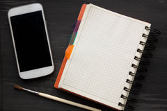 Maqueta y smartphone en la tabla negra vieja del fondo imágenes de archivo libres de regalías
