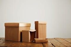 Maquetas de las cajas de cartón acanalado marrones en blanco foto de archivo
