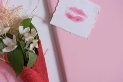 Maquette avec la carte postale et le jasmin sur le fond rose Carte et fleurs blanches gaufre pour la crème glacée, baiser de lèvr Photographie stock
