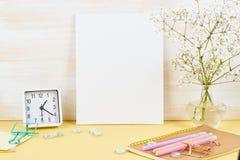 Maquette avec le cadre blanc vide sur la table jaune contre le mur en bois, alarme, fleur dans le vaze image stock