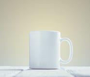 Maquette blanche de tasse inclinée sur la table en bois image libre de droits