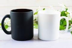 Maquette blanche et noire de tasse avec la fleur de pomme Images stock
