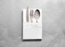 Maquette blanche vide de serviette de tissu de restaurant avec l'ensemble argenté de couverts Photos libres de droits