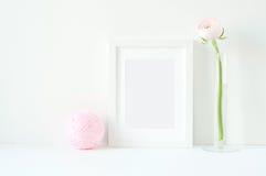 Maquette dénommée avec le cadre blanc et les ranunculos roses Photo stock
