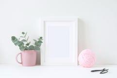 Maquette dénommée avec le cadre blanc et les ranunculos roses Photo libre de droits