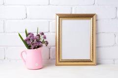 Maquette d'or de cadre avec les fleurs pourpres dans le broc rustique rose Photographie stock libre de droits