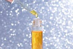 Maquette de bouteille en verre de compte-gouttes La baisse huileuse tombe de la pipette cosmétique sur le fond, la bannière ou le photo libre de droits
