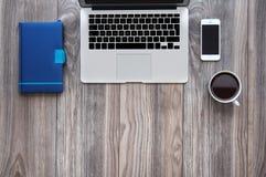 Maquette de bureau de vue supérieure avec l'ordinateur portable, le smartphone, le café et le bloc-notes Image libre de droits