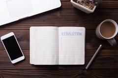 Maquette de bureau de vue supérieure : carnet, ordinateur portable, smartphone, casse-croûte, et tasse de café Nouvelle année r Images libres de droits