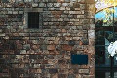 Maquette de plaque signalétique sur le mur pierreux antique dehors images stock