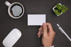 Maquette des cartes de visite professionnelle de visite blanches dans la main du ` s de l'homme Photo stock