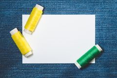 Maquette et bobines blanches des fils verts et jaunes de coton sur le fond de denim photographie stock libre de droits