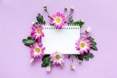Maquette florale Carnet dans le cadre des fleurs roses sur la vue supérieure de fond pourpre Images stock