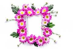 Maquette florale Feuille de papier dans le cadre des fleurs roses sur la vue supérieure de fond blanc Photos stock
