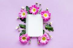 Maquette florale Feuille de papier dans le cadre des fleurs roses sur la vue supérieure de fond pourpre Photo libre de droits