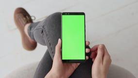 Maquette principale de chroma avec l'écran vert au téléphone portable de la jeune femme à la maison clips vidéos