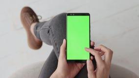 Maquette principale de chroma avec l'écran vert au téléphone portable de la jeune femme à la maison banque de vidéos