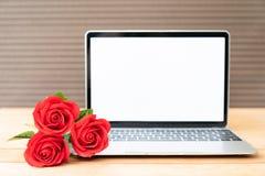 Maquette rouge de rose et d'ordinateur portable sur le bois image stock
