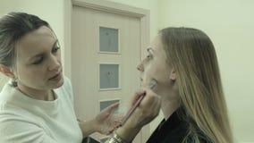 Maquilhador fêmea que aplica a composição em um cliente vídeos de arquivo