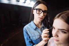Maquilhador hábil agradável que guarda a escova do olho fotos de stock royalty free
