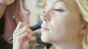 Maquilhador novo que aplica o ocultador na cara modelo do ` s fotografia de stock