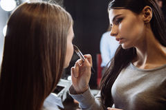 Maquilhador novo sério que trabalha com um modelo fotografia de stock royalty free
