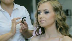 Maquilhador profissional que aplica a cara de creme tonal da jovem mulher filme