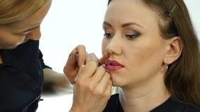 Maquilhador profissional que aplica o contorno nos bordos do modelo cosméticos da indústria da moda vídeos de arquivo
