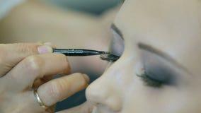 Maquilhador profissional que aplica o lápis e a escova do olho à pálpebra loura dos modelos para fazer setas da pálpebra vídeos de arquivo