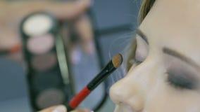 Maquilhador profissional que aplica o pó tonal à pálpebra loura dos modelos para fazer a sombra para os olhos filme