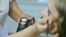 Maquilhador profissional que aplica o pó tonal à pálpebra loura dos modelos para fazer a sombra para os olhos vídeos de arquivo