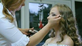 Maquilhador profissional que aplica o pó tonal à pálpebra loura dos modelos para fazer a sombra para os olhos video estoque