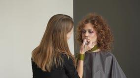 Maquilhador profissional que aplica o pó tonal aos modelos louros do cabelo longo da onda com pálpebra azul filme