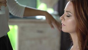 Maquilhador profissional que trabalha com jovem mulher bonita video estoque