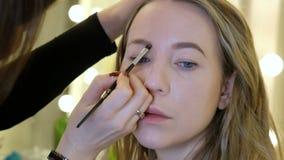Maquilhador profissional que trabalha com jovem mulher bonita, fim acima video estoque