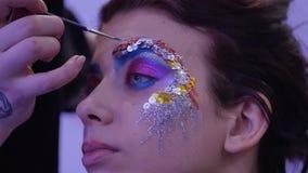 Maquilhador profissional que trabalha com jovem mulher bonita O modelo faz a composição onde pintou seus bordos, olhos video estoque