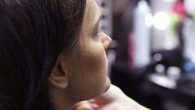 Maquilhador que aplica a fundação tonal cosmética seca na cara usando a escova da composição filme