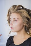 Maquilhador que aplica a fundação tonal líquida na cara da mulher Fotografia de Stock