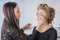 Maquilhador que aplica a fundação tonal líquida na cara da mulher Imagens de Stock Royalty Free