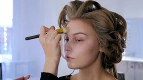 Maquilhador que aplica a fundação tonal líquida na cara do ` s da mulher Imagem de Stock