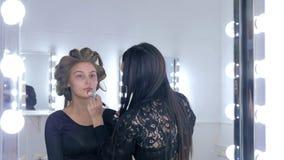Maquilhador que aplica a fundação tonal líquida na cara do ` s da mulher Fotografia de Stock